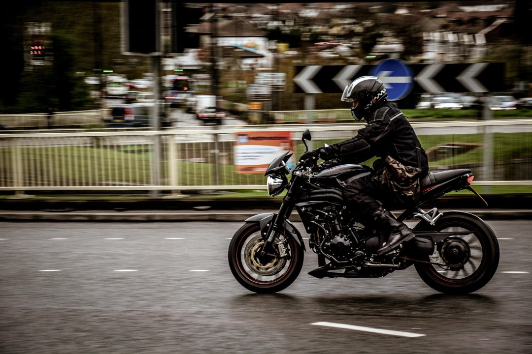 Motorcycle rider wearing all black apparel